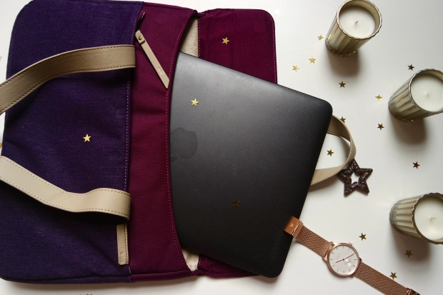 STM Grace Laptop Bag with Macbook inside and three candles and a rose gold watch on the side