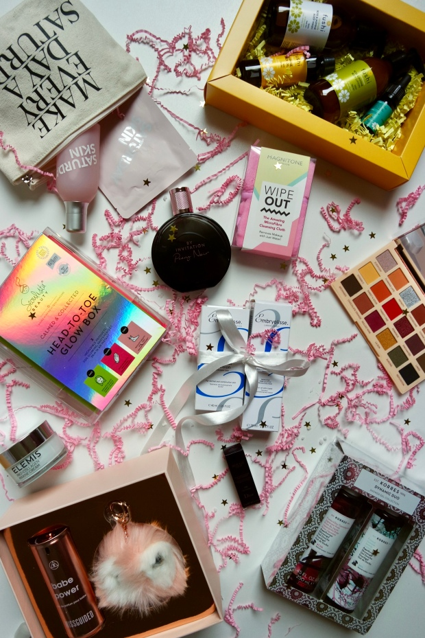 Beauty Christmas Gift Guide Flatlay of products on white background with pink confetti around